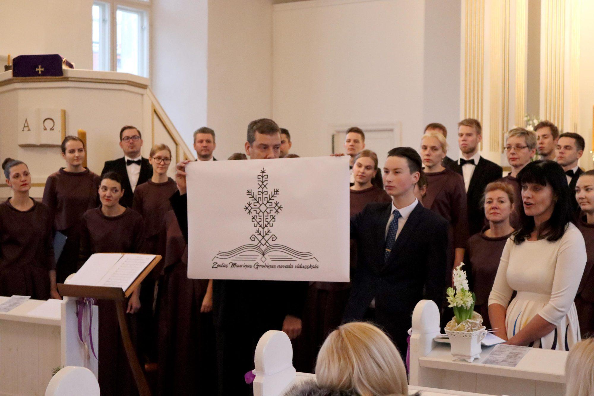 Grobiņas skolas simbolā pūcītes vietā Austras koks