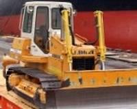 Izkraujot sojas miltus, buldozerus cilā kā rotaļlietas