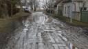 В центре города в грязи застряла машина. Жители жалуются на плохое состояние улиц с гравийным покрытием